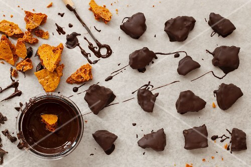 Pieces of honeycomb being dipped in dark melted chocolate