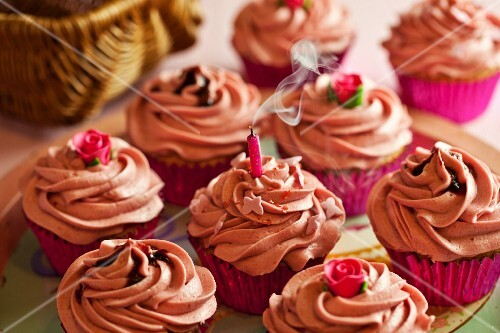 Cupcakes decorated with pink buttercream icing with a blown out, smoking candle