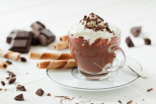 A cup of hot chocolate topped with cream and grated chocolate along with broken chocolate and wafer curls