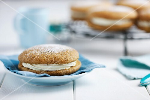 A pumpkin and ginger whoopie pie dusted with icing sugar on a blue napkin (USA)