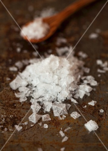 Sea salt crystals on a baking tray with a wooden spoon