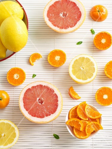 Various citrus fruits (whole, halved and sliced)