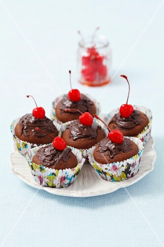 Chocolate muffins decorated with chocolate glaze and cocktail cherries