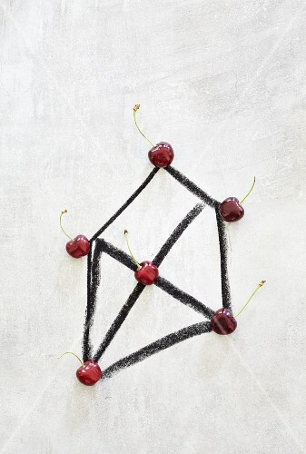 A geometric shape with cherries marking the corners