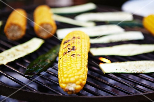Corn cobs and courgettes on a barbecue
