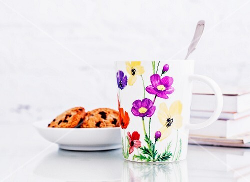 A milk mug decorated with flowers, cookies and some books on a glass table