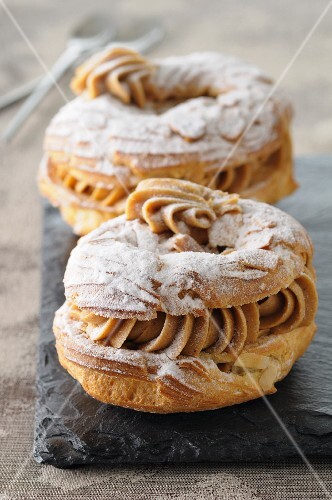 Paris Brest (choux pastries with hazelnut cream, slivered almonds and icing sugar, France)