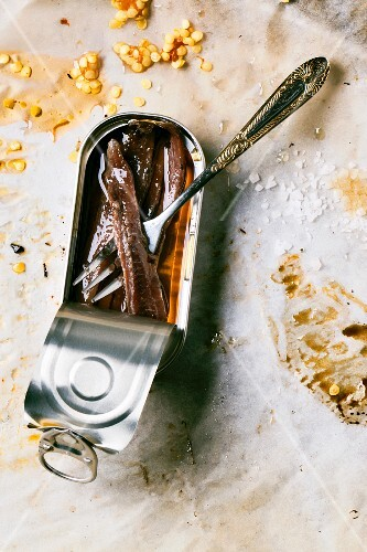 An open can of anchovies on dirty baking paper