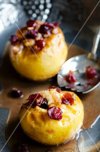 Two baked apples with cranberries on a pewter dish with a silver spoon