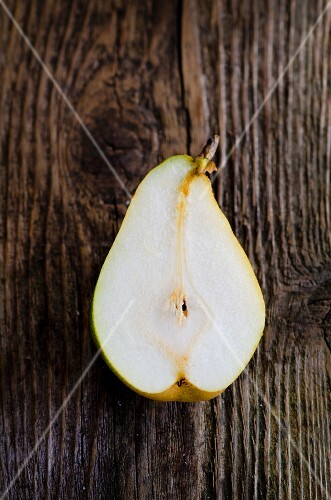 Half a pear on on wooden surface