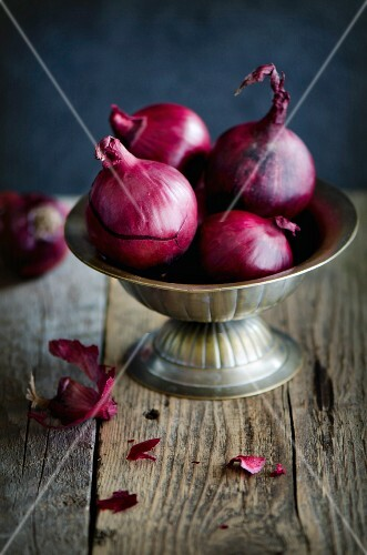 Red onions in a metal bowl on a wooden surface