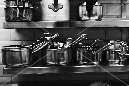 Cooking utensils on a stainless steel shelf