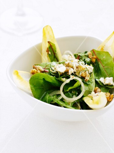 A mixed leaf salad with walnuts and onions