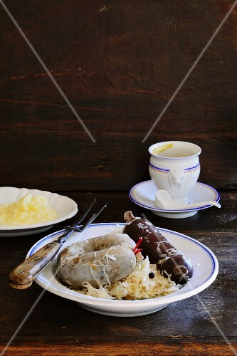 Black pudding and liver sausage with sauerkraut and mashed potatoes with a pot of mustard in the background