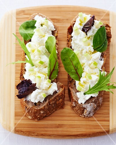 Slices of bread topped with cream cheese and herbs