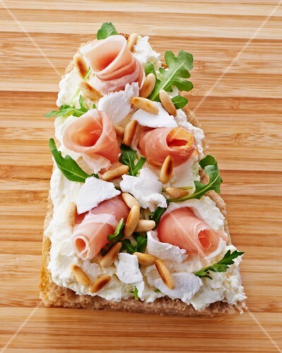 A slice of bread topped with cream cheese, prosciutto, rocket and pinenuts