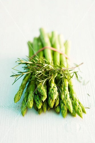 A bunch of green asparagus and a sprig of rosemary