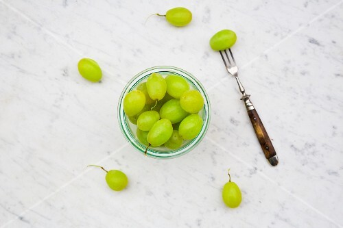 Green grapes in a glass on a marble surface