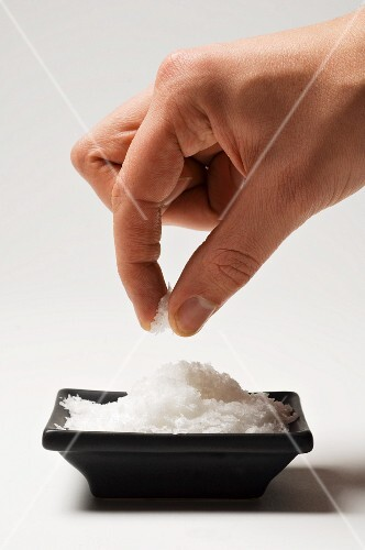 A hand taking a pinch of salt from a dish