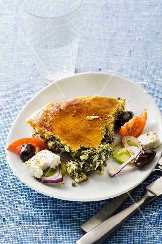 A slice of spinach pie with Greek salad