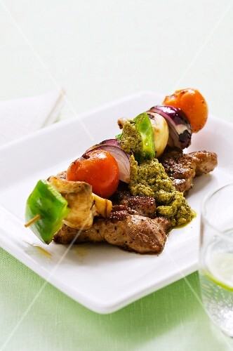 A pork chop served with a grilled vegetable skewer and pesto