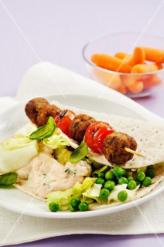 A falafel and tomato skewer on unleavened bread with peas and hummus