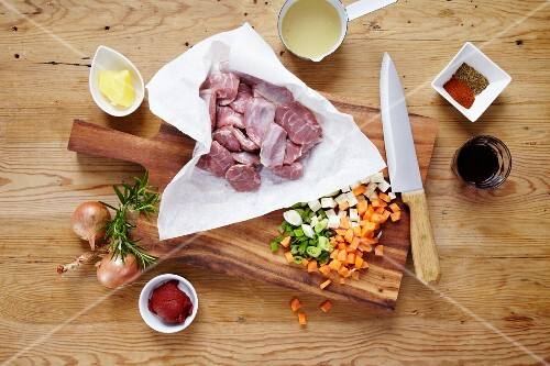 Raw pork cheeks with ingredients on a wooden table