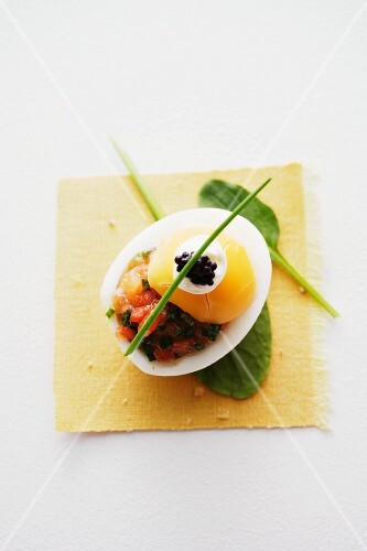 An egg with salmon tartar, crème fraîche and caviar