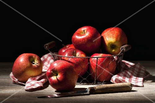 Apples in wire basket with a checked napkin and a knife
