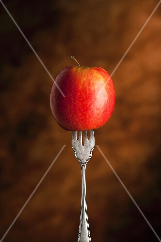 A red apple skewered on a fork