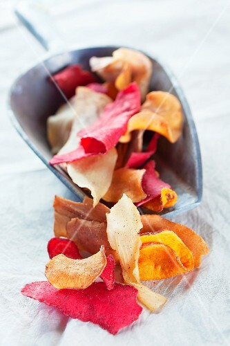 Colourful vegetable chips in a metal scoop