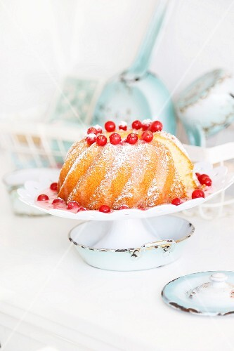 Bundt cake with redcurrant sauce on a white cake stand