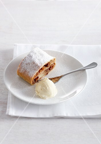 A slice of apple strudel with icing sugar and vanilla ice cream