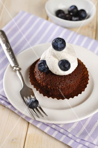 Chocolate muffin topped with cream and blueberries