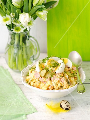 A vegetable salad with mayonnaise, ham and egg