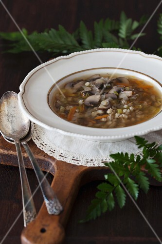 Mushroom and barley soup on a wooden board
