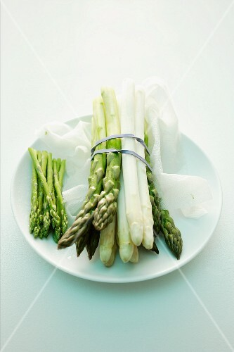 Green and white and wild asparagus bundled together on a plate