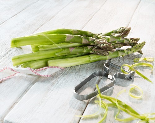 Green asparagus with a peeler on a wooden surface