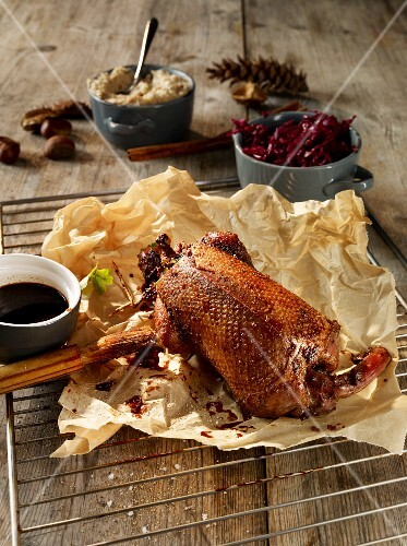 Cinnamon duck on a piece of baking paper with red cabbage and a soy sauce marinade