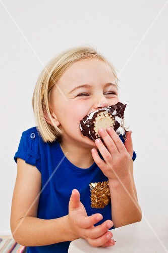 A little girl taking a big bite out of a chocolate marshmallow