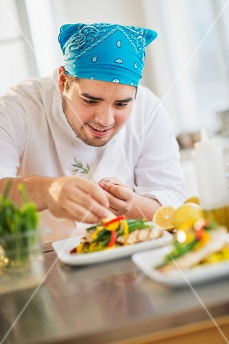 A chef garnishing a dish