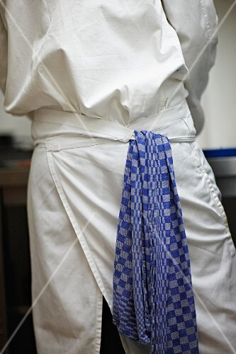 A chef with a tea towel hanging from his apron