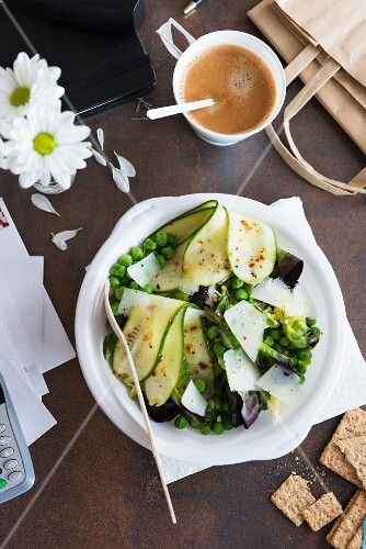 Pea and courgette salad with Parmesan, crisp bread and a cup of coffee in an office