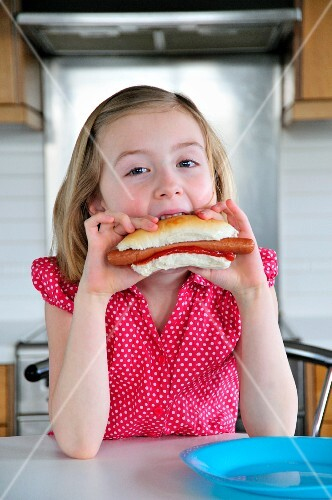 A little girl eating a hot dog