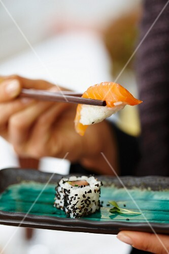 A person eating salmon sushi in a restaurant