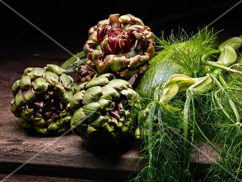 Artichokes, courgettes and dill on a wooden table