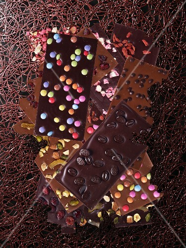 Chocolate bars with colourful chocolate beans, pistachios and mocca beans