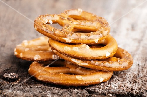 A stack of salted pretzels on a wooden surface