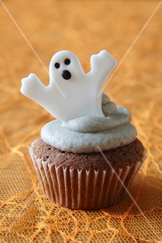 A cupcake decorated with a ghost for Halloween