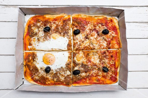 Homemade pizza with tuna, olives and a fried egg